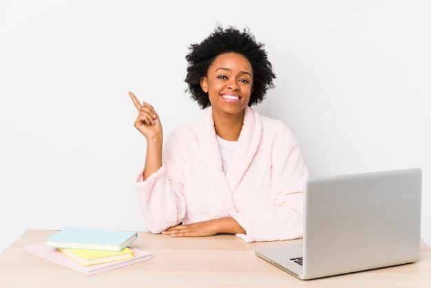 La donna afroamericana di mezza età che lavora a casa ha isolato sorridere allegramente indicando con l'indice via.