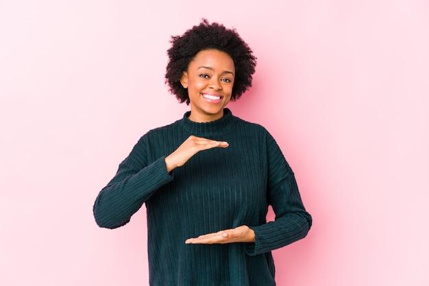 La donna afroamericana di mezza età contro un fondo rosa ha isolato la tenuta qualcosa con entrambe le mani, presentazione del prodotto.