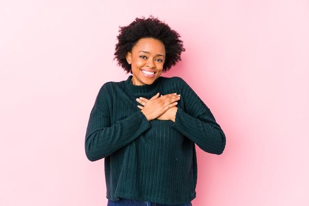 La donna afroamericana di mezza età su uno sfondo rosa isolato ha un'espressione amichevole, premendo il palmo sul petto. concetto di amore.