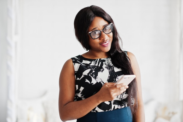 La donna afroamericana graziosa in occhiali ha posato nella sala con il telefono cellulare a disposizione.