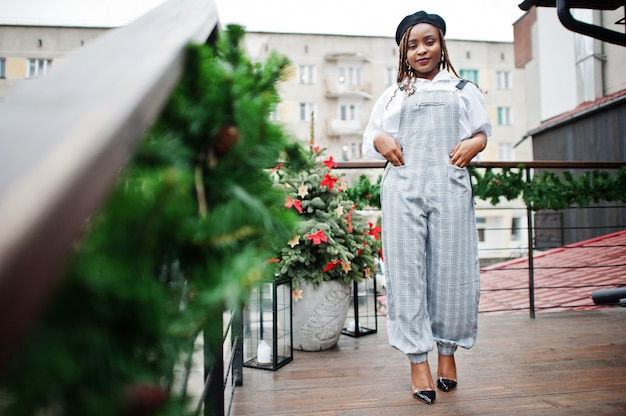 La donna afroamericana in camici e berretto ha posato in terrazzo all'aperto con le decorazioni di natale e l'albero del nuovo anno.