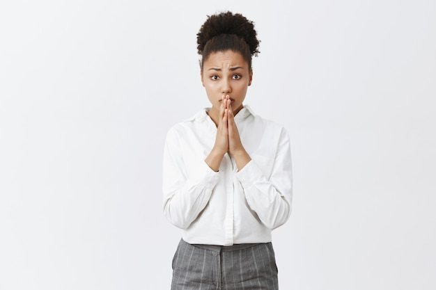 La donna afroamericana preoccupata e speranzosa chiede il favore, la donna di affari ha bisogno di aiuto
