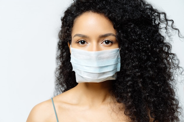 La donna afroamericana seria cerca di fermare il virus e la malattia epidemica, rimane a casa durante l'epidemia infettiva, indossa una maschera medica, isolata su sfondo bianco, ricoverata in ospedale, diagnosticata