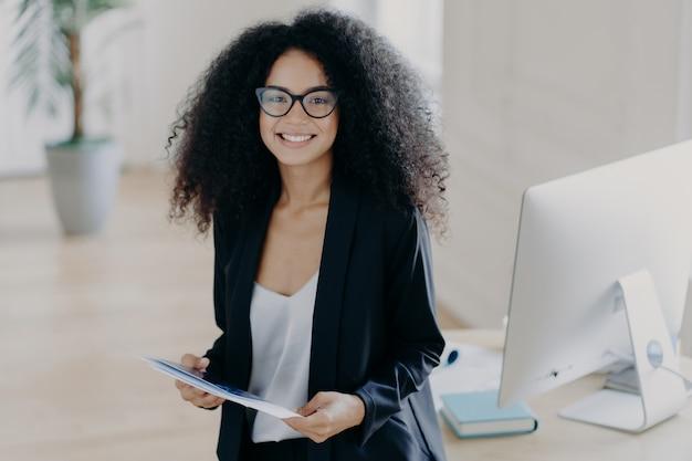 La donna afroamericana tiene alcune carte, indossa abiti e occhiali eleganti