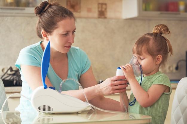 La donna aiuta a respirare attraverso la maschera al bambino