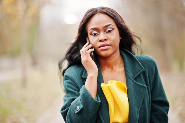 La donna alla moda dell'afroamericano al cappotto verde ed al vestito giallo ha proposto contro la sosta di autunno e parlare sul telefono.