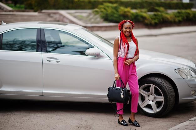 La donna alla moda di affari dell'afroamericano ai pantaloni dentellare ed i timori rossi ha proposto all'aperto con il sacchetto contro la sua automobile di lusso.