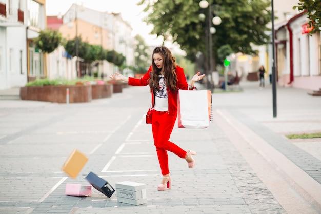 La donna alla moda in vestito rosso con i sacchetti della spesa ha lasciato cadere i contenitori di scarpe nella via.