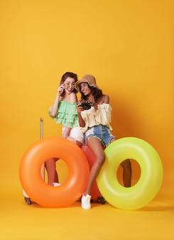 La donna allegra degli amici si è vestita in vestiti dell'estate che si siedono su una valigia e su un anello di gomma