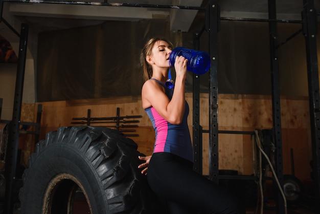 La donna allegra in palestra beve l'acqua