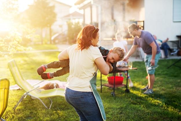 La donna allegra in un grembiule porta in giro il figlio piccolo mentre ride e il resto della famiglia griglia.