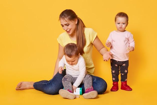 La donna allegra stanca gioca con i suoi bambini divertenti attivi che sono in congedo di maternità.