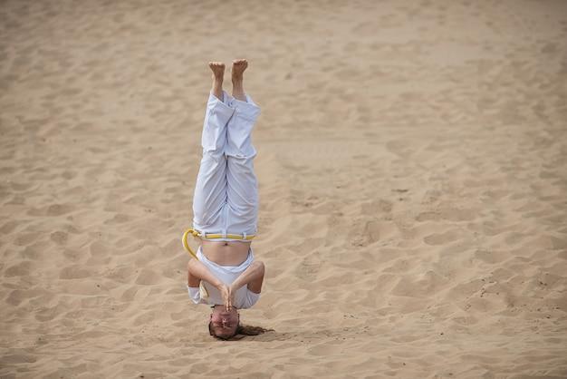 La donna allena capoeira all'aria aperta. la ragazza esegue un calcio