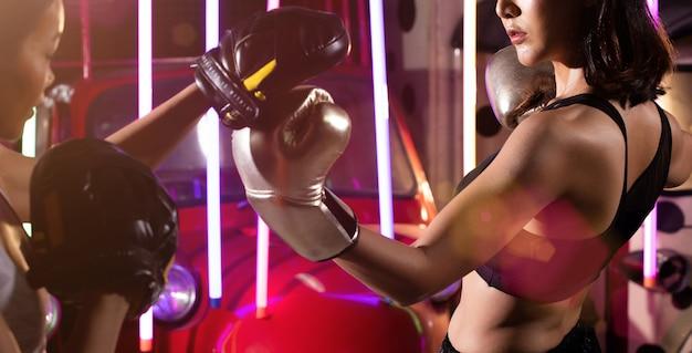 La donna allena la palestra moderna al neon del pugile di pugilato di esercizio