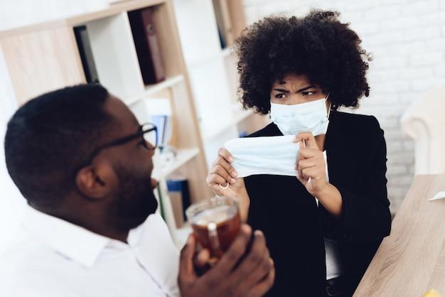 La donna americana dà maschera medica al collega malato.