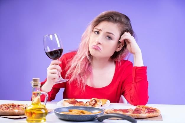 La donna annoiata in camicetta rossa si siede al tavolo con un bicchiere di vino rosso