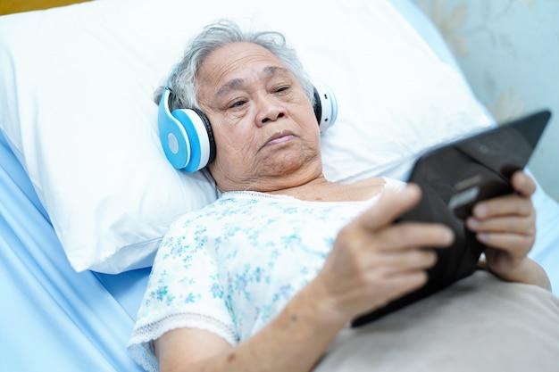 La donna anziana asiatica che tiene la compressa digitale sul letto ed ascolta musica mentre si riposa.