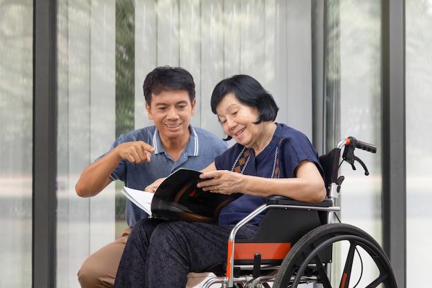 La donna anziana che legge un libro sulla sedia a rotelle con suo figlio si prende cura.