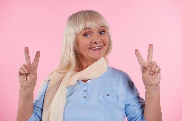 La donna anziana felice mostra il segno di vittoria. segno di pace.