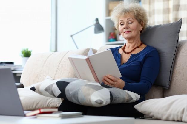 La donna anziana si siede sul divano di casa e legge il libro
