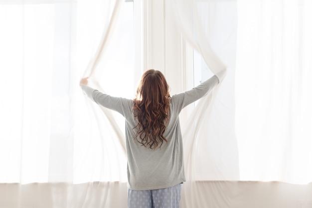 La donna apre le tende al mattino