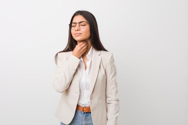 La donna araba di giovani affari isolata contro un bianco soffre il dolore alla gola a causa di un virus o di un'infezione.