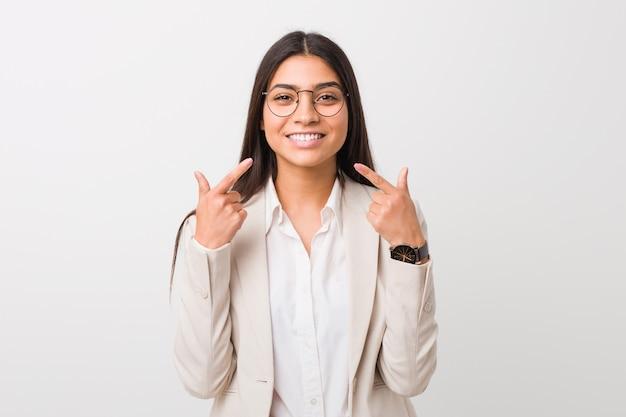 La donna araba di giovani affari isolata contro una priorità bassa bianca sorride, indicando le dita alla bocca.