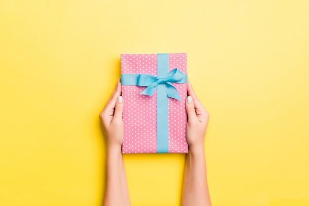 La donna arma la tenuta del contenitore di regalo con il nastro colorato sulla tavola gialla