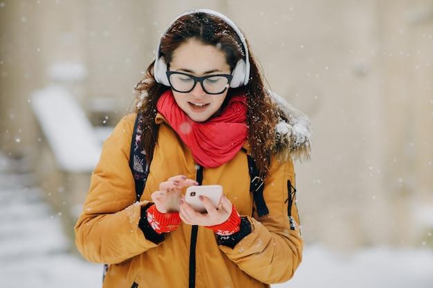 La donna ascolta musica sul telefono cellulare nella città all'orario invernale. ritratto di close-up giovane donna in inverno città, sorridente