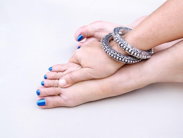 La donna asiatica adulta con le unghie dei piedi blu e indossa il profitto sul polso, usa il massaggio delle mani sui piedi per rilassarsi.