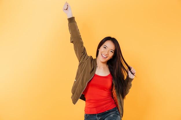 La donna asiatica allegra in rivestimento si rallegra e l'esame della macchina fotografica