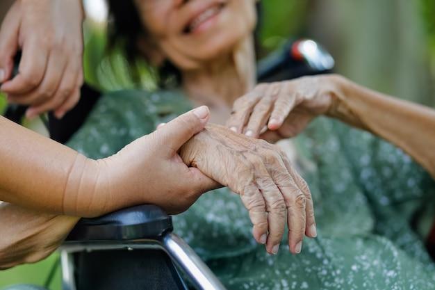La donna asiatica anziana sulla sedia a rotelle a casa con la figlia ciao