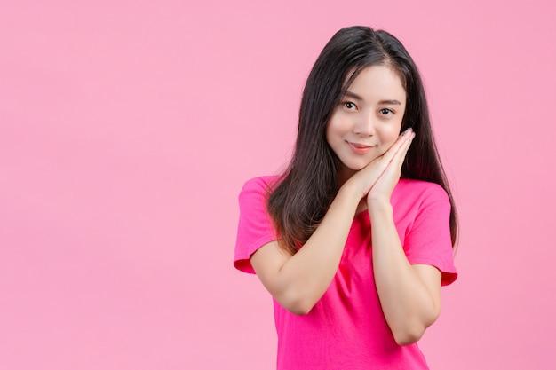 La donna asiatica bianca sveglia posa timida su un rosa.