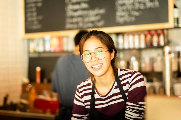 La donna asiatica che amiling lavora nel cibo del piccolo imprenditore e beve il caffè.