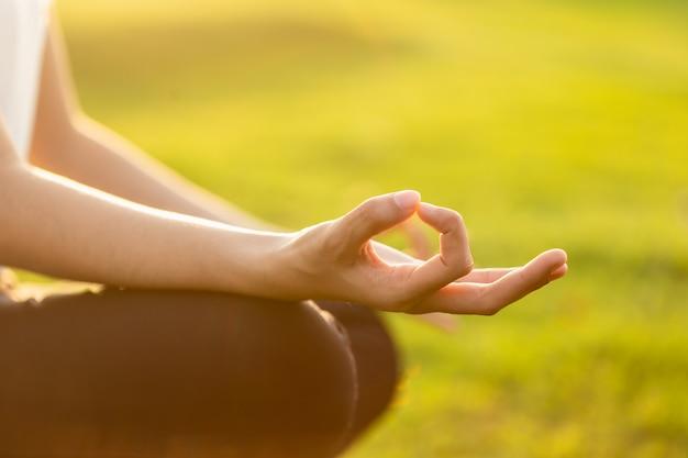 La donna asiatica che fa l'yoga si esercita nel parco