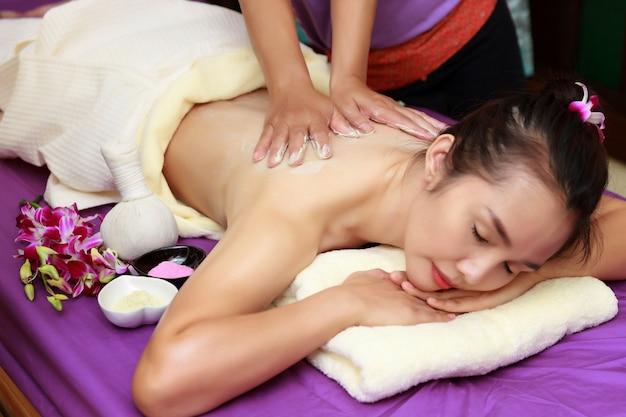 La donna asiatica che gode di un sale sfrega il massaggio alla stazione termale.