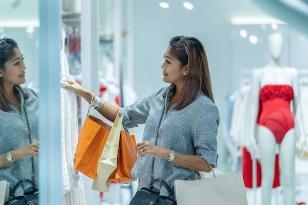 La donna asiatica che guarda e che sceglie la biancheria intima nel deposito compera con l'azione felice al centro di dipartimento
