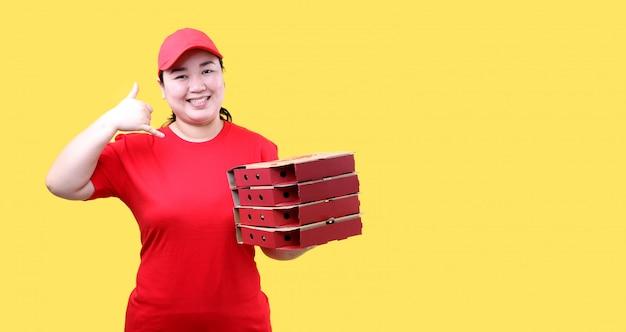 La donna asiatica che indossa un cappello rosso invita la pizza italiana ad essere ordinata in una scatola di cartone separata su una parete gialla