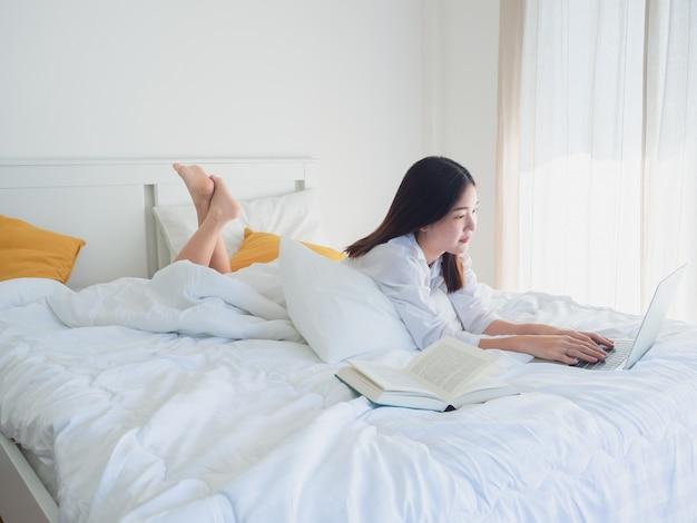 La donna asiatica che per mezzo del computer e legge il libro sul letto di mattina
