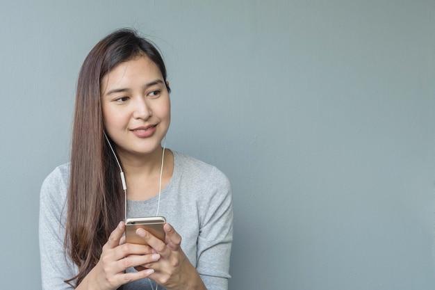 La donna asiatica che si siede per ascolta musica dal ridurre in pani con il trasduttore auricolare nell'emozione felice sulla parete vaga del cemento