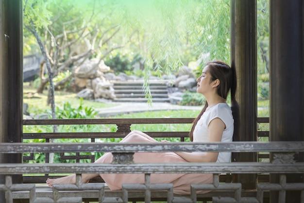 La donna asiatica che si siede sulla sedia di legno nel parco pubblico per si rilassa il tempo