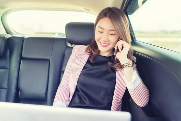 La donna asiatica che sorride e parla dal cellulare che chiama sul telefono cellulare