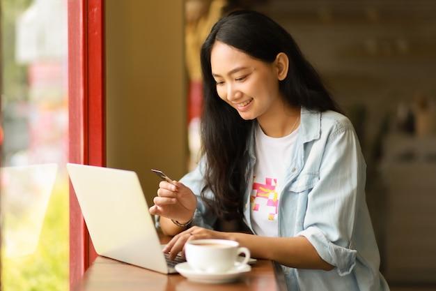 La donna asiatica che usando il computer portatile funziona e beve il caffè in caffè