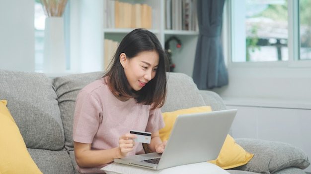 La donna asiatica che utilizza il commercio elettronico di acquisto della carta di credito e del computer portatile, femmina si rilassa sentendosi l'acquisto online felice che si siede sul sofà nel salone a casa. le donne di stile di vita si rilassano a casa concetto.