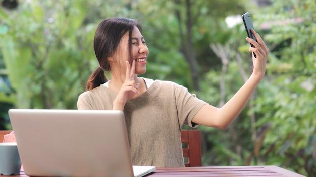 La donna asiatica che utilizza la posta del selfie del telefono cellulare nei media sociali, femmina si rilassa sentendo i sacchetti della spesa di mostra felici che si siedono sulla tavola nel giardino nella mattina.