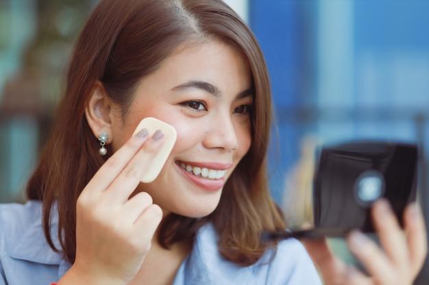 La donna asiatica compone il suo fronte con rossetto in caffè