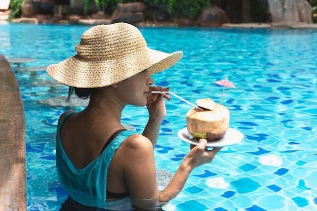 La donna asiatica con il cappello che mangia la noce di cocco beve nella piscina
