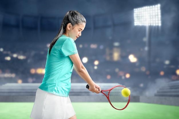 La donna asiatica con una racchetta da tennis in mano ha colpito la palla