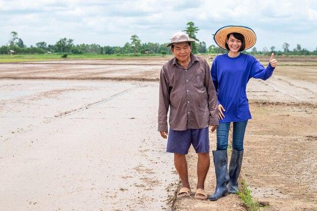 La donna asiatica del coltivatore e il padre dell'uomo del vecchio contadino sorridono e stanno alla fattoria del riso