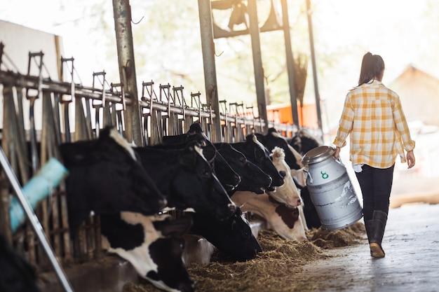La donna asiatica del coltivatore sta tenendo un contenitore di latte nella sua fattoria. a piedi fuori dalla fattoria